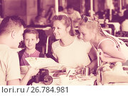 Купить «Cheerful parents with two kids relaxing in cafe», фото № 26784981, снято 24 июля 2017 г. (c) Яков Филимонов / Фотобанк Лори