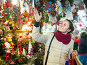 woman choosing Christmas decoration at market in evening time, фото № 26785177, снято 24 августа 2017 г. (c) Яков Филимонов / Фотобанк Лори