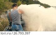 Купить «A man looks at a smoking engine of a broken car», видеоролик № 26793397, снято 21 августа 2017 г. (c) Илья Шаматура / Фотобанк Лори