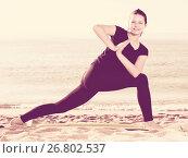 Smiling adult woman in black T-shirt is practicing yoga. Стоковое фото, фотограф Яков Филимонов / Фотобанк Лори