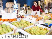 Купить «Glad young customer selecting fruits in grocery», фото № 26802729, снято 1 марта 2017 г. (c) Яков Филимонов / Фотобанк Лори