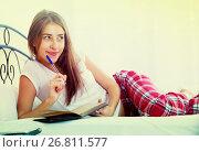 Купить «Smiling girl making shopping list in bedroom», фото № 26811577, снято 16 августа 2018 г. (c) Яков Филимонов / Фотобанк Лори