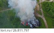 Купить «Пожар в сельской местности, горящие деревянные постройки, вид сверху», видеоролик № 26811797, снято 16 июля 2017 г. (c) Кекяляйнен Андрей / Фотобанк Лори