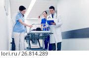 Купить «medics with woman on hospital gurney at emergency», фото № 26814289, снято 3 декабря 2015 г. (c) Syda Productions / Фотобанк Лори