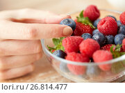 Купить «close up of young woman hand with berries in bowl», фото № 26814477, снято 28 апреля 2015 г. (c) Syda Productions / Фотобанк Лори