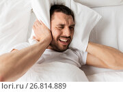 man in bed with pillow suffering from noise. Стоковое фото, фотограф Syda Productions / Фотобанк Лори