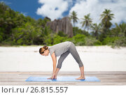 Купить «woman making yoga intense stretch pose on beach», фото № 26815557, снято 13 ноября 2015 г. (c) Syda Productions / Фотобанк Лори