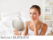 Купить «beautiful woman with mirror sitting on bed at home», фото № 26816013, снято 9 апреля 2017 г. (c) Syda Productions / Фотобанк Лори