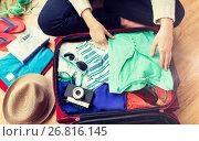 Купить «close up of woman packing travel bag for vacation», фото № 26816145, снято 9 февраля 2016 г. (c) Syda Productions / Фотобанк Лори