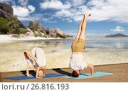 Купить «couple making yoga over tropical beach background», фото № 26816193, снято 7 августа 2016 г. (c) Syda Productions / Фотобанк Лори