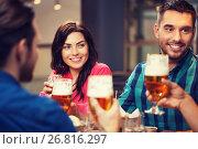 Купить «friends dining and drinking beer at restaurant», фото № 26816297, снято 8 ноября 2015 г. (c) Syda Productions / Фотобанк Лори