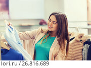 Купить «happy young woman choosing clothes in mall», фото № 26816689, снято 19 февраля 2016 г. (c) Syda Productions / Фотобанк Лори