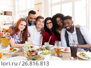 Купить «happy friends eating at restaurant», фото № 26816813, снято 2 мая 2017 г. (c) Syda Productions / Фотобанк Лори