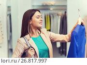 Купить «happy young woman choosing clothes in mall», фото № 26817997, снято 19 февраля 2016 г. (c) Syda Productions / Фотобанк Лори