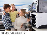 Купить «Portrait of happy family selecting microwave», фото № 26818717, снято 22 августа 2018 г. (c) Яков Филимонов / Фотобанк Лори