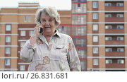 Elderly woman talks using a smart phone outdoors. Стоковое видео, видеограф worker / Фотобанк Лори