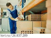 Купить «Shop assistant man is checking quality of bricks», фото № 26837289, снято 26 июля 2017 г. (c) Яков Филимонов / Фотобанк Лори