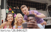 Купить «happy young friends taking selfie at food truck», видеоролик № 26844621, снято 20 июня 2018 г. (c) Syda Productions / Фотобанк Лори