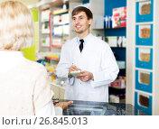 Helpful pharmacist serving young woman in pharmacy. Стоковое фото, фотограф Яков Филимонов / Фотобанк Лори