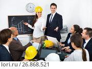 Купить «Smiling professionals with laptops and helmets having working meeting», фото № 26868521, снято 7 декабря 2019 г. (c) Яков Филимонов / Фотобанк Лори