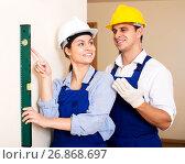 Купить «Constructor showing assistant measuring the wall», фото № 26868697, снято 21 марта 2019 г. (c) Яков Филимонов / Фотобанк Лори
