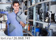 Купить «Man 35-40 years old is choosing plastic trumpet in plumbing department», фото № 26868741, снято 26 июля 2017 г. (c) Яков Филимонов / Фотобанк Лори