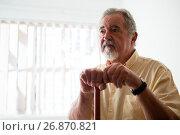 Купить «Thougtful senior man looking away while holding walking cane», фото № 26870821, снято 28 апреля 2017 г. (c) Wavebreak Media / Фотобанк Лори
