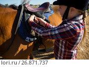 Купить «Close-up of girl adjusting saddle on horse», фото № 26871737, снято 3 мая 2017 г. (c) Wavebreak Media / Фотобанк Лори