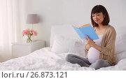 Купить «happy pregnant asian woman reading book in bed», видеоролик № 26873121, снято 27 июня 2019 г. (c) Syda Productions / Фотобанк Лори