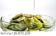 Купить «The cucumbers cut by thin slices with garlic in ware from glass sprinkle ground pepper and pour with olive oil», видеоролик № 26873229, снято 27 августа 2017 г. (c) Anatoly Timofeev / Фотобанк Лори