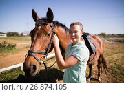 Купить «Portrait of female jockey fastening bridle», фото № 26874105, снято 3 мая 2017 г. (c) Wavebreak Media / Фотобанк Лори