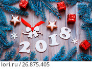 Купить «Happy New Year 2018 background with 2018 figures, Christmas toys, blue fir tree branches. New Year 2018 still life», фото № 26875405, снято 29 ноября 2016 г. (c) Зезелина Марина / Фотобанк Лори