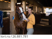 Купить «Female jockey using smart phone while standing by horse», фото № 26881781, снято 3 мая 2017 г. (c) Wavebreak Media / Фотобанк Лори
