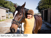 Купить «Portrait of smiling female jockey stroking horse», фото № 26881789, снято 3 мая 2017 г. (c) Wavebreak Media / Фотобанк Лори