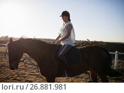 Купить «Female jockey riding horse at barn», фото № 26881981, снято 3 мая 2017 г. (c) Wavebreak Media / Фотобанк Лори