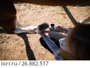 Купить «Overhead view of woman attaching shoe on horse foot», фото № 26882517, снято 3 мая 2017 г. (c) Wavebreak Media / Фотобанк Лори