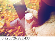 Купить «woman with tablet pc and coffee in autumn park», фото № 26885433, снято 12 октября 2016 г. (c) Syda Productions / Фотобанк Лори