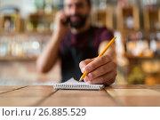 Купить «bartender with notebook and pencil at bar», фото № 26885529, снято 8 декабря 2016 г. (c) Syda Productions / Фотобанк Лори