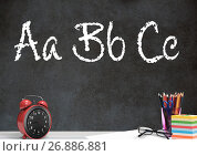 Desk foreground with blackboard graphics of ABC spelling. Стоковое фото, агентство Wavebreak Media / Фотобанк Лори