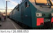 Железнодорожный локомотив грузового состава проходит вдоль перрона станции (2017 год). Редакционное видео, видеограф Кекяляйнен Андрей / Фотобанк Лори