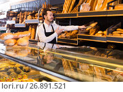 Купить «Male shop assistant demonstrating delicious loaves of bread in bakery», фото № 26891521, снято 26 января 2017 г. (c) Яков Филимонов / Фотобанк Лори