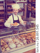 Купить «Skillful male pastry maker demonstrating croissant», фото № 26891545, снято 26 января 2017 г. (c) Яков Филимонов / Фотобанк Лори