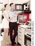 Купить «Positive husband with wife looking new microwave», фото № 26893821, снято 15 июня 2017 г. (c) Яков Филимонов / Фотобанк Лори