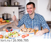 Купить «young man eating pizza and salad in the kitchen at home», фото № 26906785, снято 29 марта 2016 г. (c) Татьяна Яцевич / Фотобанк Лори
