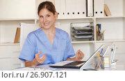 Купить «Female doctor working with medical records in office», видеоролик № 26907121, снято 9 августа 2017 г. (c) Яков Филимонов / Фотобанк Лори
