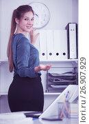 Купить «Female entrepreneur looking for documents on shelves», фото № 26907929, снято 31 июля 2017 г. (c) Яков Филимонов / Фотобанк Лори