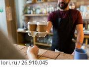 Купить «man or bartender serving customer at coffee shop», фото № 26910045, снято 8 декабря 2016 г. (c) Syda Productions / Фотобанк Лори