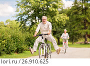 happy senior couple riding bicycles at summer park. Стоковое фото, фотограф Syda Productions / Фотобанк Лори