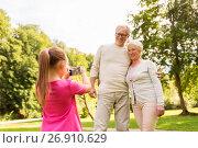 Купить «granddaughter photographing grandparents at park», фото № 26910629, снято 9 августа 2017 г. (c) Syda Productions / Фотобанк Лори