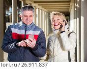 Купить «positive husband and wife go nearby with each other and speak by mobile phone», фото № 26911837, снято 20 августа 2019 г. (c) Яков Филимонов / Фотобанк Лори